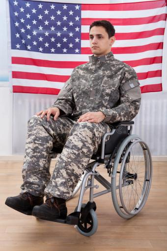 patriotic-soldier-sitting-wheel-chair-against-american-flag-full-length-46361216