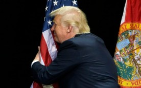 Republican presidential candidate Donald Trump pauses during his campaign speech to hug the American flag Saturday, June 11, 2016, in Tampa, Fla. (AP Photo/Chris O'Meara)