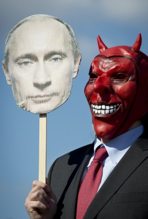An activist wears a devil's mask which he covers with a picture of Vladimir Putin as part of a protest against the Russian President outside the congress center of the Hanover trade fair on April 7, 2013 in Hanover, western Germany. Putin arrived for the official opening of the industrial trade fair with German Chancellor Angela Merkel (not in pic). Activists and critics said Putin should be held to account for a recent crackdown on non-governmental organisations promoting democratic reforms in Russia. AFP PHOTO / ODD ANDERSEN