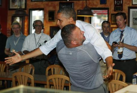 U.S. President Barack Obama holds on as he is hugged and picked up by Scott Van Duzer at Big Apple Pizza and Pasta Italian Restaurant in Fort Pierce, Florida, while campaigning across the state by bus, September 9, 2012. REUTERS/Larry Downing (UNITED STATES - Tags: POLITICS ELECTIONS)